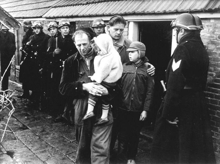 Onder gewapend geleide verlaat 'vrije boer' Hartman in 1963 met zijn kinderen de boerderij in Hollandscheveld. Achter hem Evert Harmsen, bestuurslid van de 'Vrije Boeren'. Beeld Hollandse Hoogte /  ANP