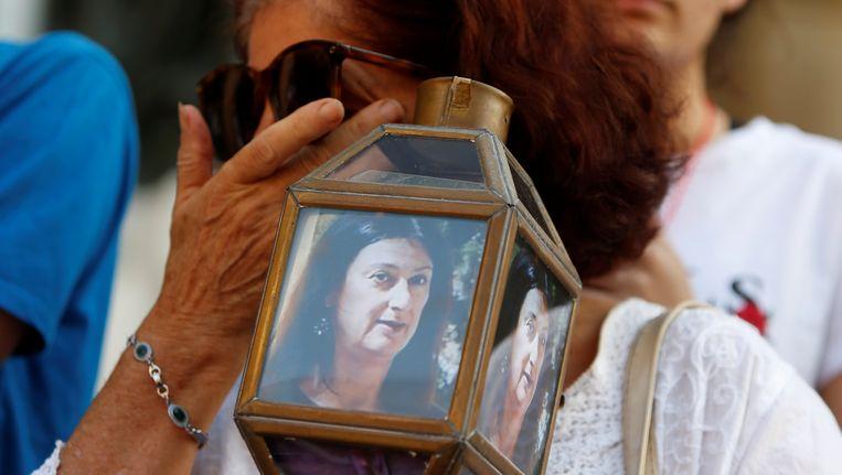 Een demonstrant houdt een lantaarn vast met een foto van de vermoorde journalist Daohne Caruana Galizia. Beeld reuters