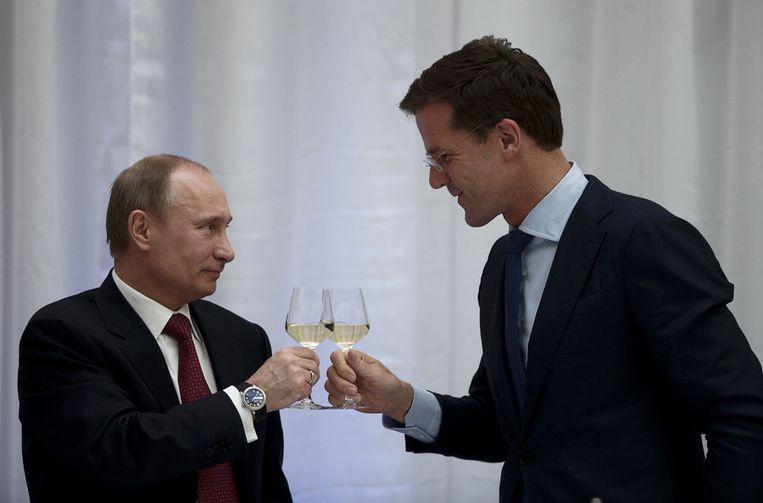 Premier Mark Rutte en de president van Rusland Vladimir Poetin heffen het glas tijdens een diner in het Scheepsvaartmuseum in Amsterdam. Beeld null
