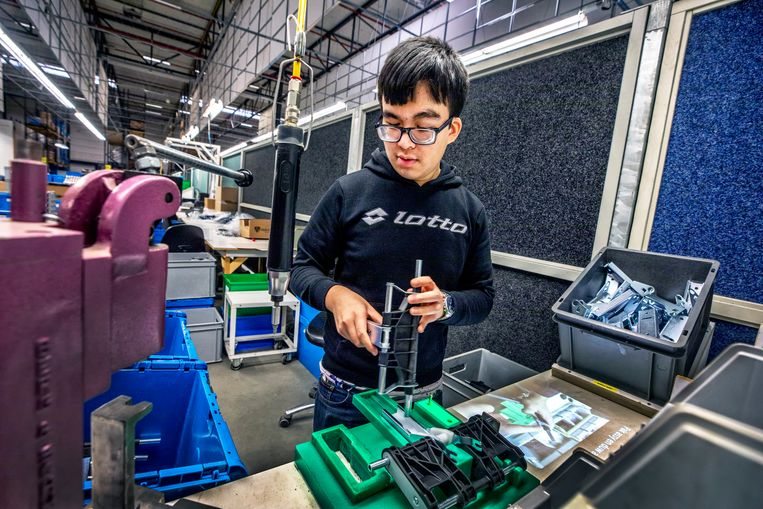 Bij werkbedrijf Senzer worden instructies voor de assemblage van Maxi Cosi's op de werkbank geprojecteerd. Beeld Raymond Rutting