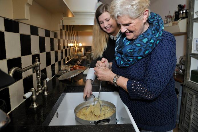 Rachel van Kommer stampt met oudtante Lia Veldhuizen-Bos de appels voor de hete bliksem.