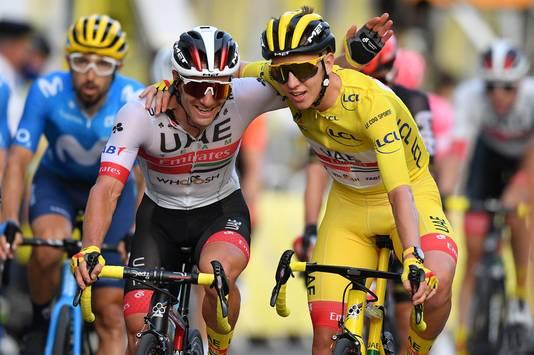 Pogacar komt in het geel over de streep in Parijs, knuffelend met een ploeggenoot.