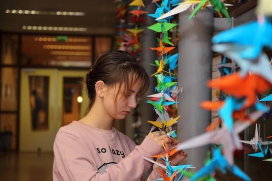 Een leerling hangt een door haar gevouwen kraanvogeltje aan het lint in de school.