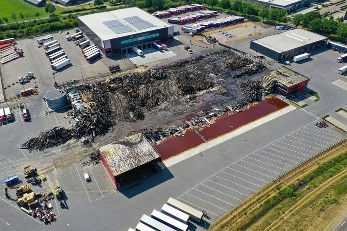 Het terrein van Van der Heijden na de brand. Van het grote overslaggebouw, centraal geleden op het terrein, bleef vrijwel niets over.