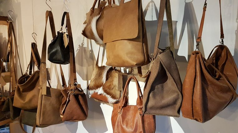 Enkele handgemaakte tassen hangen aan de muur.