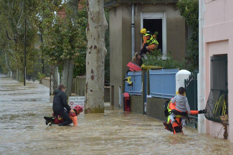 Brandweermannen helpen kinderen evacueren uit hun huizen in Trèbes.