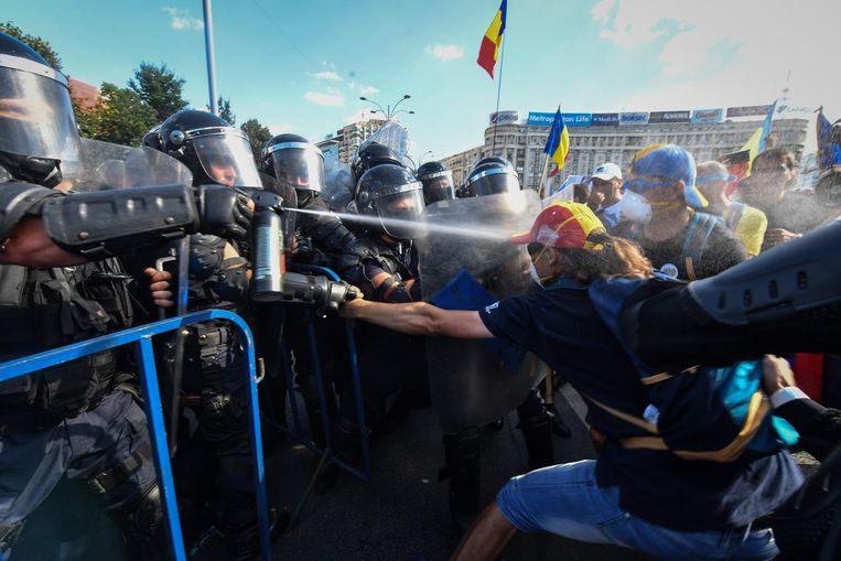 Roemeense politie vechten met demonstranten en spuiten traangas tijdens een antiregeringsprotest in Boekarest. Beeld AFP