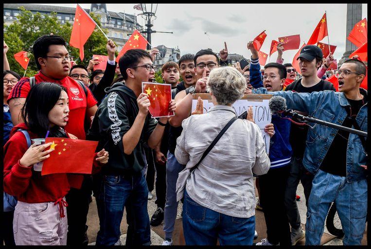 Opstootje tussen een demonstrante en een groep Chinese tegenbetogers.