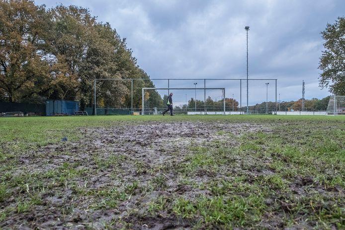 Rinie Arts loopt over het kletsnatte en kapotte voetbalveld bij Sint-Anthonis. Het ziet er naar uit dat ze voorlopig geen kunstgras krijgen.