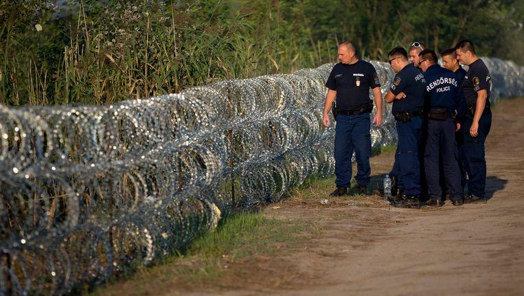 Hongaarse grenswachten bij een deel van het hek.