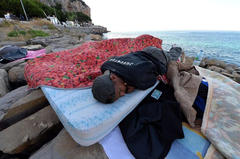 Een vluchteling slaapt op de rotspartijen in Ventimiglia. Beeld epa