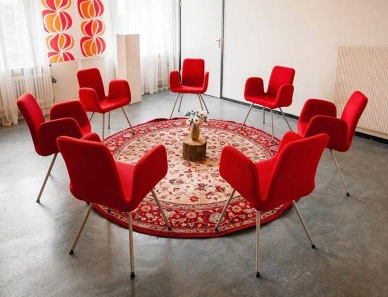 De mensen zitten op zeven rode stoelen rondom een rond tapijt. Beeld