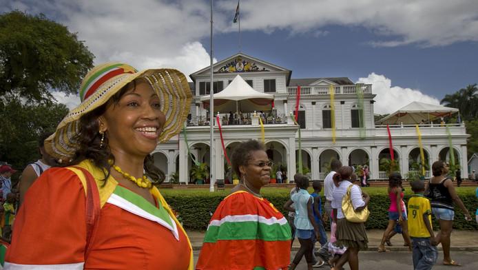 Een moeder en dochter lopen voor het presidentiële paleis langs tijdens de viering van de 32e verjaardag van de onafhankelijkheid van Suriname.