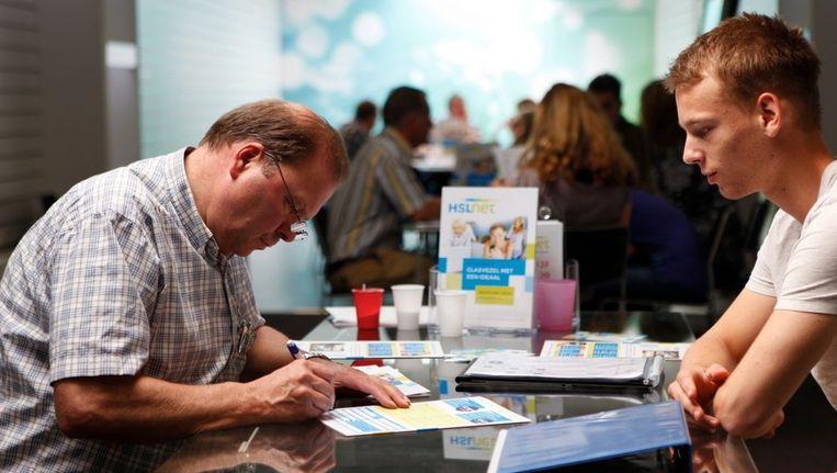 Een inwoner van Heeze-Leende tekent voor een glasvezelabonnement bij zijn lokale coöperatie HSLnet. Beeld HSLnet