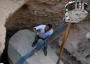 Een archeoloog op de sarcofaag die omhoog wordt getakeld.