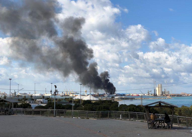 Rook stijgt op uit de haven van Tripoli nadat deze is aangevallen. Beeld REUTERS