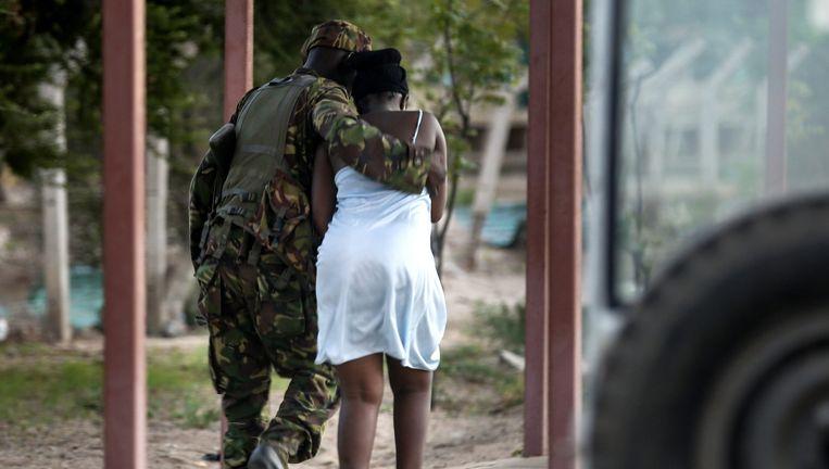 Een soldaat begeleid een jonge vrouw nadat zij is bevrijd uit een van de gebouwen van de universiteit. Beeld epa