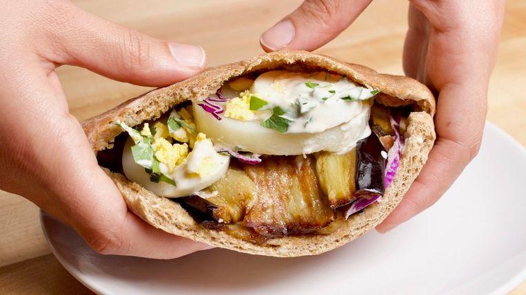 Sabich, een pitabroodje gevuld met gefrituurde aubergine, hardgekookt ei en fris-pittige mangosaus. Beeld TRBEELD