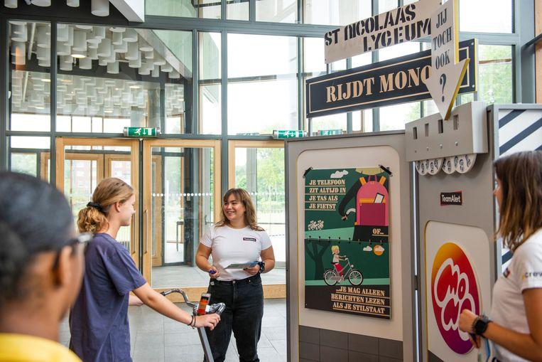 Voorlichters van Team Alert praten met leerlingen van het St. Nicolaaslyceum over het gevaar van appen op de fiets. Beeld Vera Duivenvoorden
