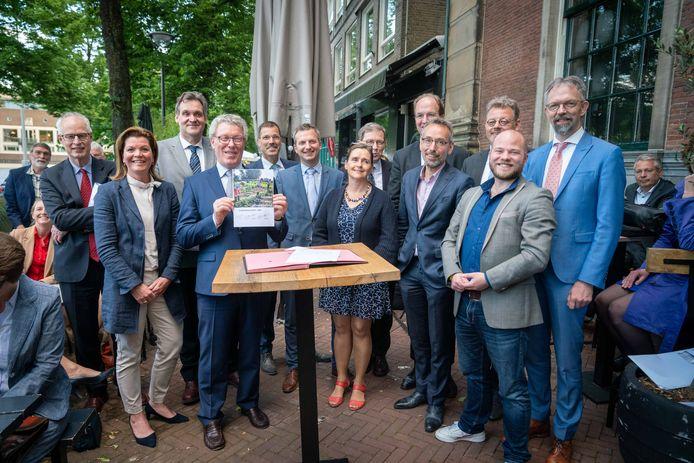 Jan Markink (VVD) presenteert trots het nieuwe coalitieakkoord. Om hem heen staan onder meer de andere nieuwe gedeputeerden van Gelderland.
