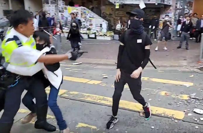 De agent schiet op een betoger.