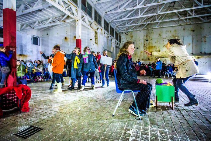Oefenen voor de voorstelling in de oude Zwitsal-fabriek. De meeste acteurs en muzikanten droegen warme jassen tegen de kou.