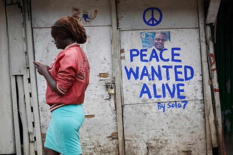Een vrouw loopt langs een bericht van straatartiest Solomon Muyundo, ook wel bekend als Solo7, in de slums van Nairobi. Beeld EPA