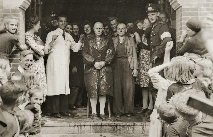 OUDEWATER, MEI 1945 In de Kapellestraat in Oudewater, destijds gelegen in Zuid-Holland en tegenwoordig onderdeel van de provincie Utrecht, worden voor het oog van de inwoners van de stad vrouwen door de lokale kapper kaalgeschoren. Na de bevrijding werden vrouwen die een relatie hadden met Duitse militairen, publiekelijk te schande gezet. Ze werden uitgescholden voor 'moffenmeiden', 'moffenhoeren' en 'moffenkleders'. Vaak werden deze vrouwen en jonge meisjes uit hun huis gesleurd en op een boerenkar door de straten gereden, bespuugd, uitgescholden, besmeurd met hakenkruizen en in het openbaar kaalgeschoren. Er zijn ook vergissingen gemaakt. In dat geval kon er aanspraak gemaakt worden op een compensatie van 200 gulden.