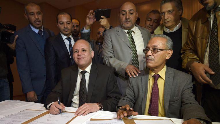 Twee politici van de rivaliserende parlementen in Libië tekenen hun akkoord, Awad Mohammed Abdul-Sadiq (L) van het door islamisten gesteunde Algemeen Nationaal Congres (GNC) in de hoofdstad Tripoli, en Ibrahim Fethi van het internationaal erkende parlement in Tobruk. De overeenkomst werd ondertekend in buurland Tunesië. Beeld afp