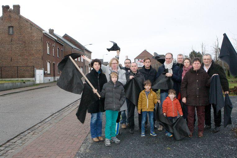 De leden van de actiegroep Tienen Stinkt met hun zwarte vlaggen.