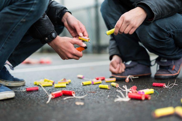 Twee jongens steken rotjes af op straat. Beeld ANP XTRA