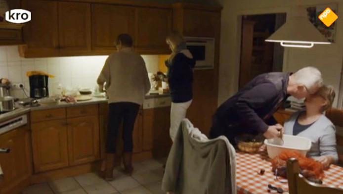 Geert zoent Mary, terwijl Ada en Hetty bij het fornuis staan.
