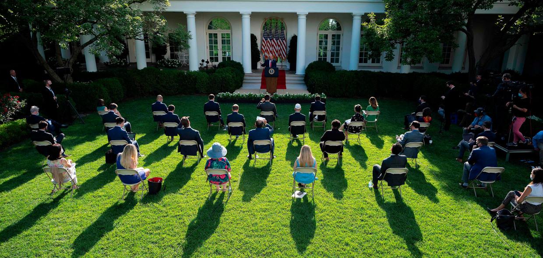 Journalisten luisteren op 14 juli in de bloedhitte naar een lange toespraak van president Trump. Beeld AFP