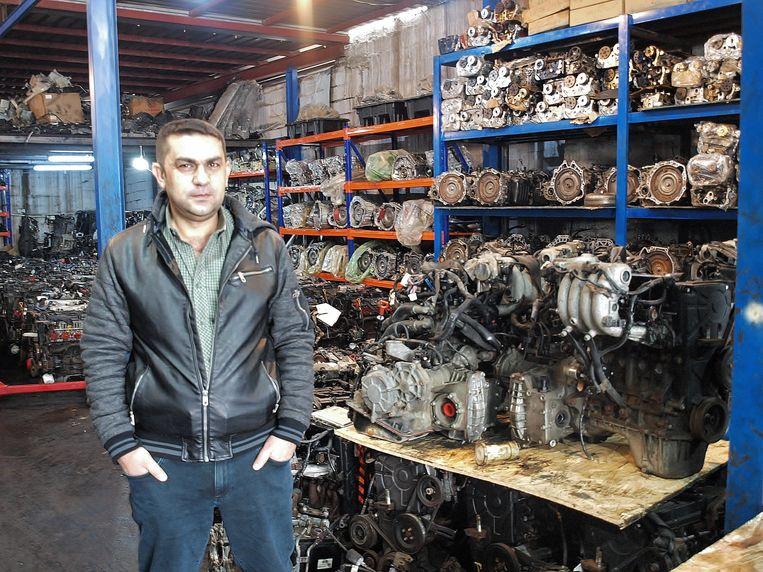 Importeur Omar Said poseert in de loods van een klant bij onderdelen die hij importeerde.  Beeld Judit Neurink