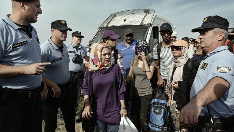 Kroatische agenten begeleiden vluchtelingen die uit Servië zijn aangekomen bij de grens. Beeld Daniel Rosenthal