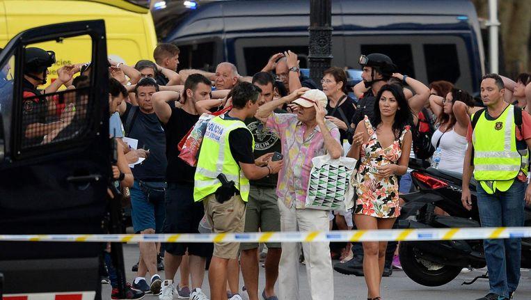 Politiemannen houden een identiteitscontrole bij de Ramblas. Beeld AFP