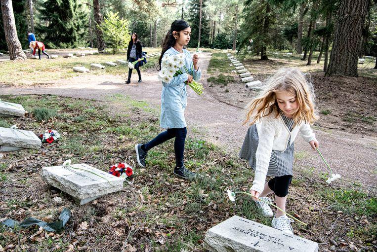 Kinderen leggen bloemen op de graven van het ereveld in Loenen. Voor het eerste is het ereveld dicht tijdens Dodenherdenking.  Beeld Koen Verheijden