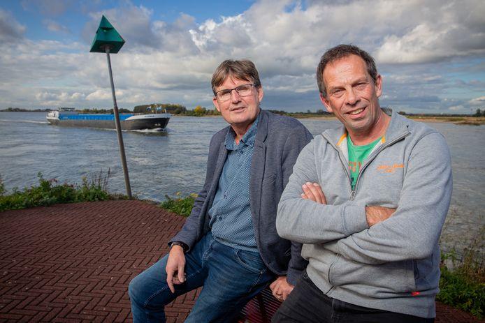Dick Sonneveld (links) en Jan Willem Drost aan de Waal bij Druten. 'Er zitten bij ons meer mensen dan in de Ewaldenkerk.'