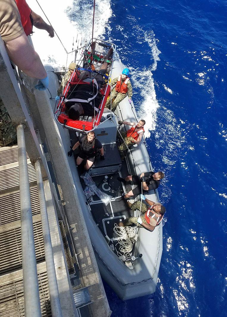 Een geredde migrant wordt aan boord gehaald van de USNS Trenton.