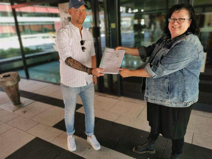 Martijn van Butselaar (l) neemt namens Arnhem Centraal de petitie met meer dan 5.000 handtekeningen tegen het Arnhemse afvalbeleid in ontvangst van Bettina Achterhuis. Van Butselaar geeft de handtekeningen door aan de gemeenteraad.