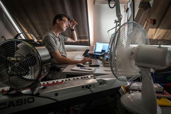 Verslaggever Nico Schapendonk veegt het zweet van zijn voorhoofd tijdens het tikken van een stuk op zijn thuiskantoor op zolder. Corona of niet, het nieuws ligt niet stil.