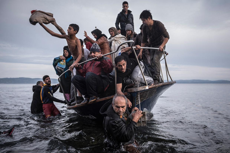 Migranten arriveren met een Turkse boot op het Griekse eiland Lesbos. Door gebrekkige samenwerking in de EU is de doorstroom hier zeer traag. Beeld Sergey Ponomarev / AP