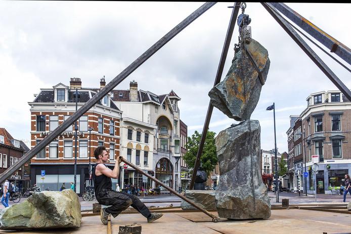 Performance-kunstenaar Nick Steur stapelt en balanceert stenen op het Neude in Utrecht. Hij is in mei te zien in de Oude Warande.