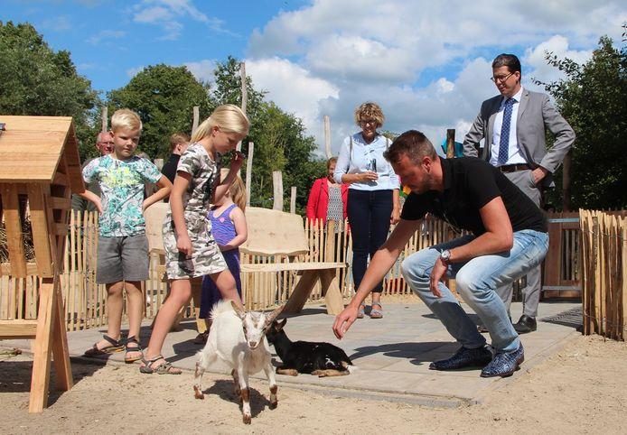 Wethouder Maikel van der Neut in het kinderboerderijdeel van Hof van Eckberge, door de knieën bij een dwerggeitje.