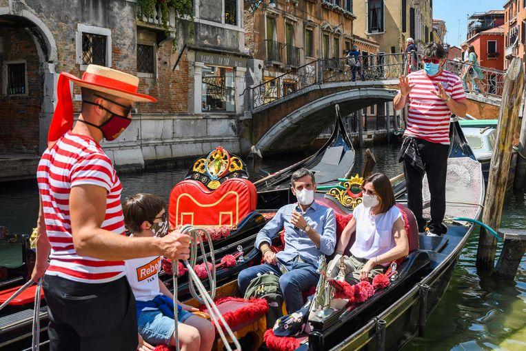 Toeristen genieten van een rondvaart in een traditionele gondel.  Beeld AFP