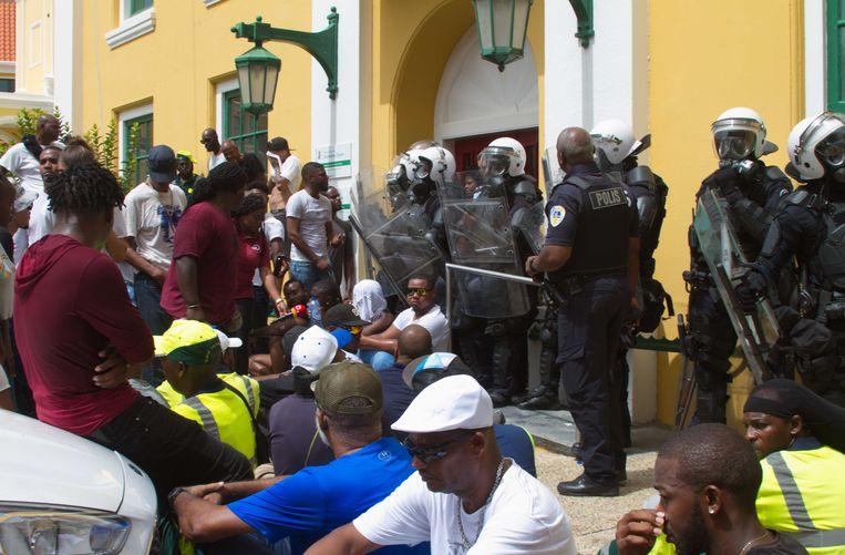 Deelnemers tijdens een manifestatie voor het regeringsgebouw. Er zijn verscheidene mensen gearresteerd voor hun rol bij plunderingen en brandstichtingen in de binnenstad van Willemstad. De betogers eisen het aftreden van minister-president Eugene Rhuggenaath. Beeld ANP