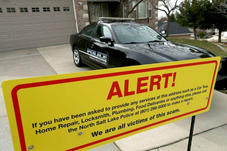 Een bord met een waarschuwing en een politiewagen voor de woning van Walt Gilmore in Salt Lake City. Het hele gezin werd vijftien maanden lang geteisterd door een cyberstalker.