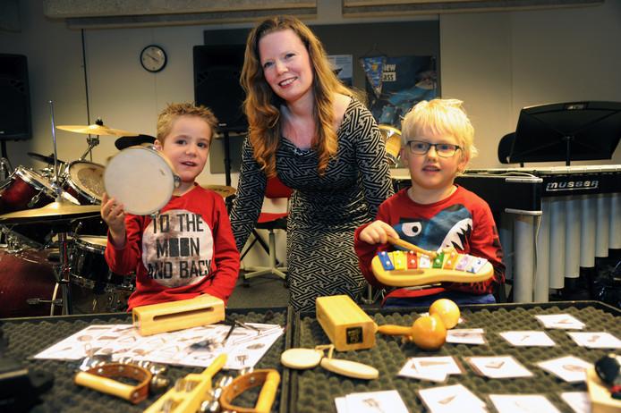 Angelique Koerts tussen Hidde (l) en Oscar tijdens de percussieles voor kleuters van de Zeeuwse muziekschool in Middelburg.