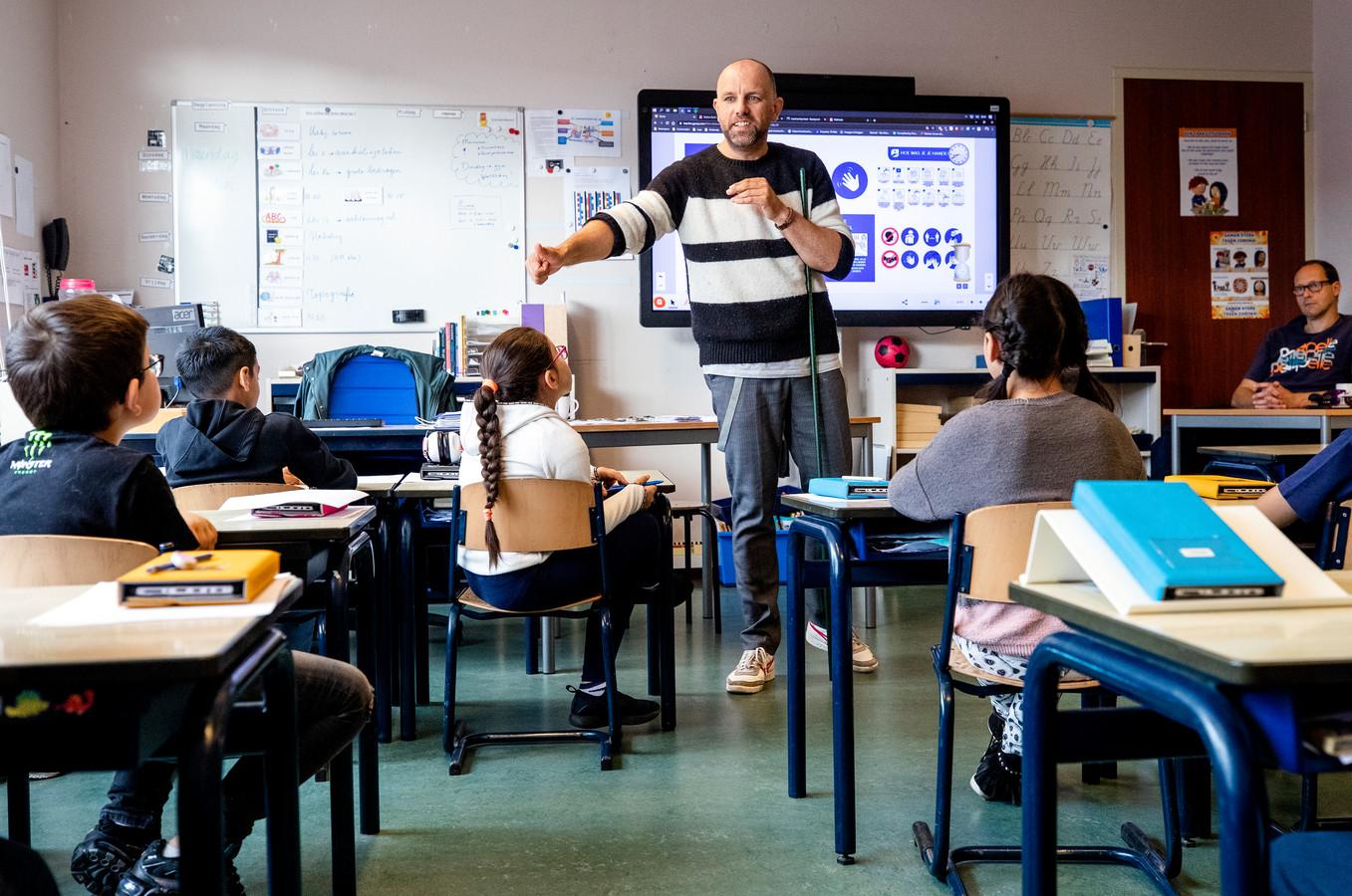 Een leraar laat in de klas aan basisschoolleerlingen zien wat de coronamaatregelen zijn. Doordat veel leraren zich ziek moeten melden, is er veel lesuitval.
