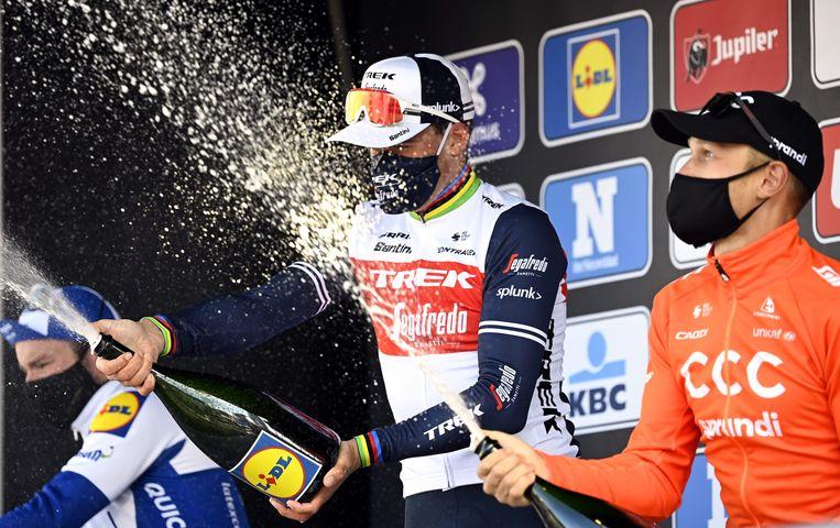 De Deen Mads Pedersen ontkurkt de champagne na zijn winst in Gent-Wevelgem. Op twee en drie eindigden Matteo Trentin en Florian Sénéchal.  Beeld AFP